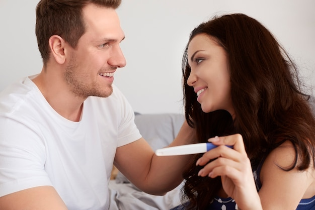 Casal feliz olhando para o teste de gravidez