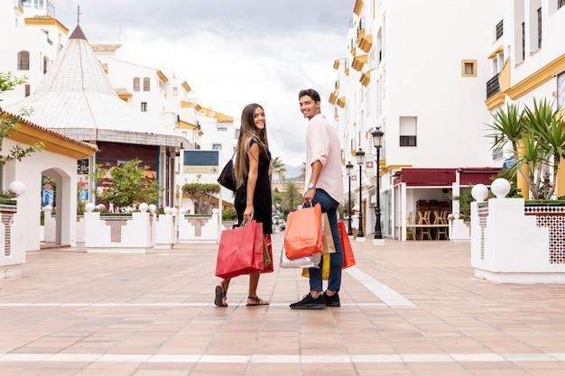 Casal feliz olhando para trás com sacos