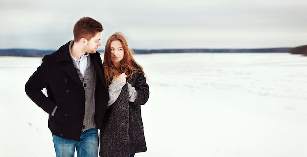 Casal feliz passear ao longo do prado nevado