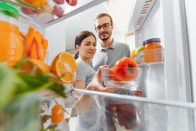 Casal feliz perto de geladeira aberta com legumes e frutas. conceito de nutrição saudável.