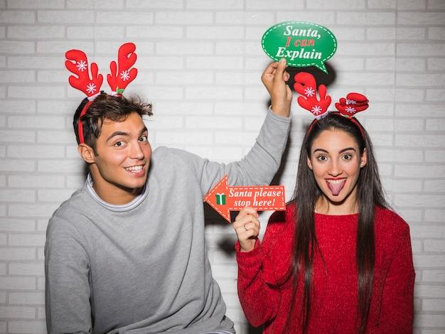 Casal feliz posando com adesivos de natal