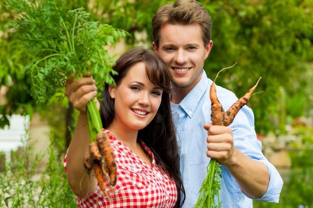 Casal feliz posando com as cenouras que acabaram de colher