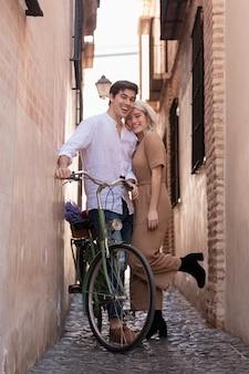 Casal feliz posando com bicicleta fora