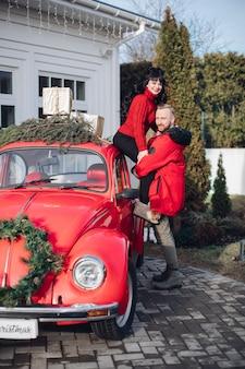 Casal feliz posando com um carro vintage vermelho decorado com galhos de árvores de abeto e presentes de natal.
