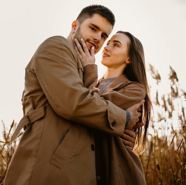 Casal feliz posando de baixo ângulo
