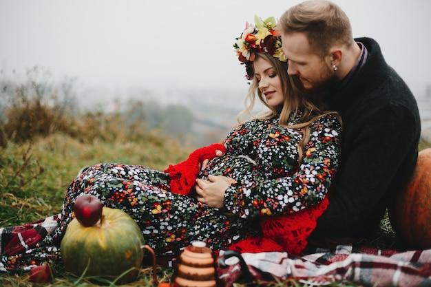 Casal feliz pregant aproveita seu tempo juntos, deitado sobre a lei