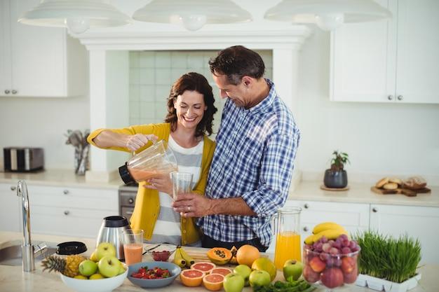 Casal feliz preparando smoothie na cozinha