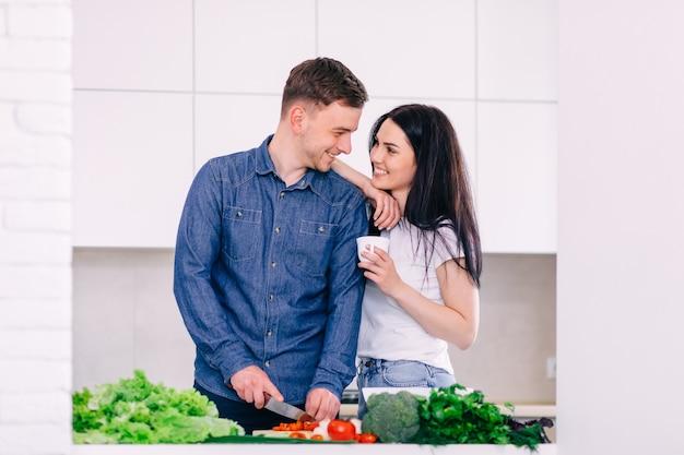 Casal feliz preparando um delicioso almoço na cozinha. menina segurando uma xícara de café.