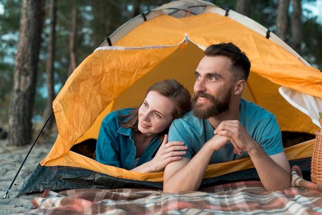 Casal feliz que estabelece na tenda