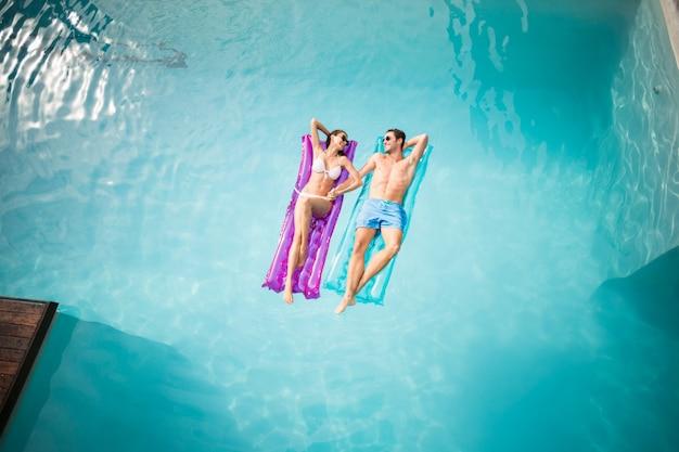 Casal feliz relaxando na balsa inflável na piscina
