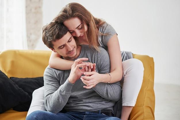 Casal feliz relaxando no sofá amarelo na sala de estar de sua nova casa.