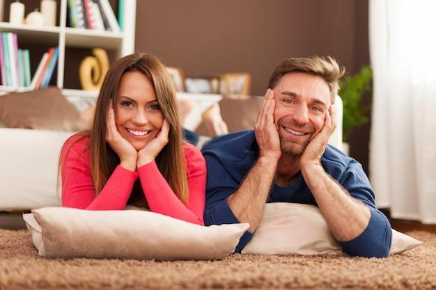 Casal feliz relaxando no tapete em casa