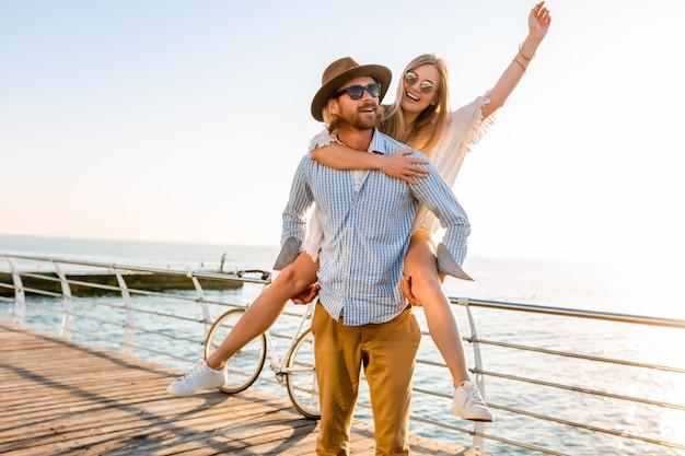 Casal feliz rindo viajando no verão pelo mar, homem e mulher usando óculos escuros