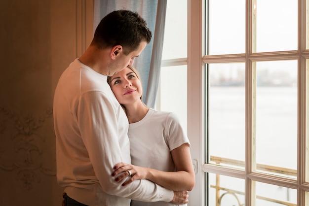 Casal feliz romântico abraçado ao lado da janela