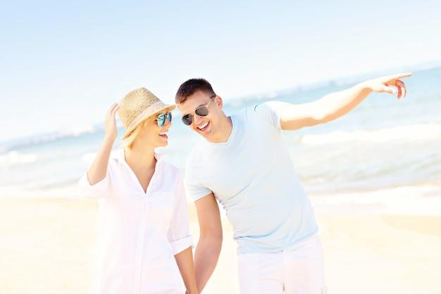 Casal feliz romântico caminhando na praia na polônia