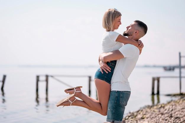 Casal feliz saindo juntos na praia