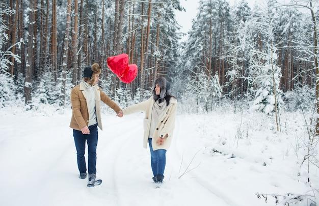 Casal feliz se abraçando e beijando ao ar livre na floresta de inverno. balões em forma de coração