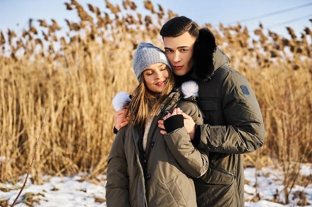 Casal feliz se abraçando e rindo ao ar livre no inverno. vapor fotográfico anunciando roupas de inverno