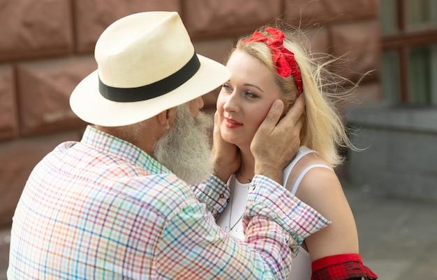 Casal feliz se abraçando e rindo ao ar livre.