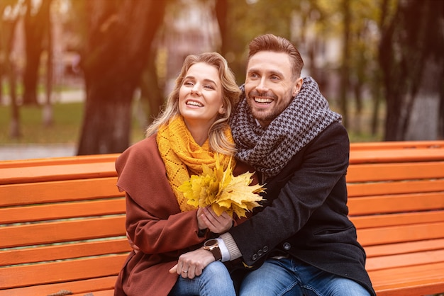 Casal feliz se abraçando encantador, sentado no banco, romântico se abraçando no parque usando casacos e lenços