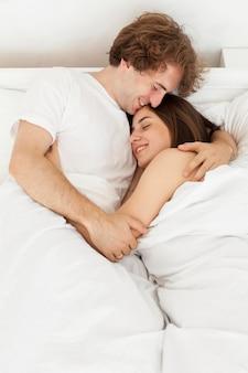Casal feliz se abraçando na cama tiro médio