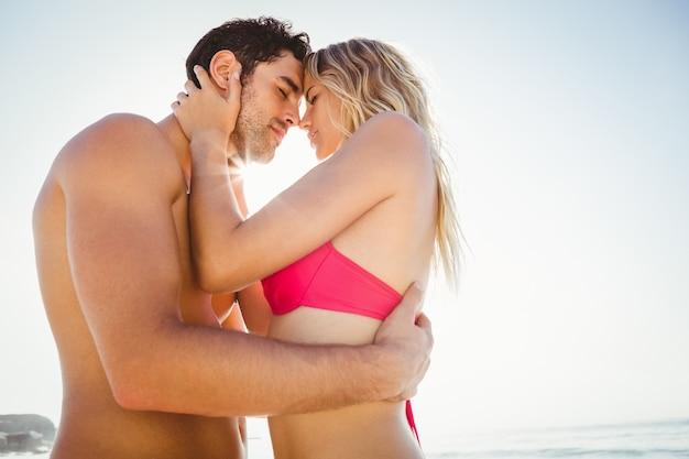 Casal feliz se abraçando na praia
