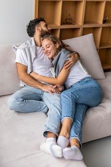 Casal feliz se abraçando no sofá em casa