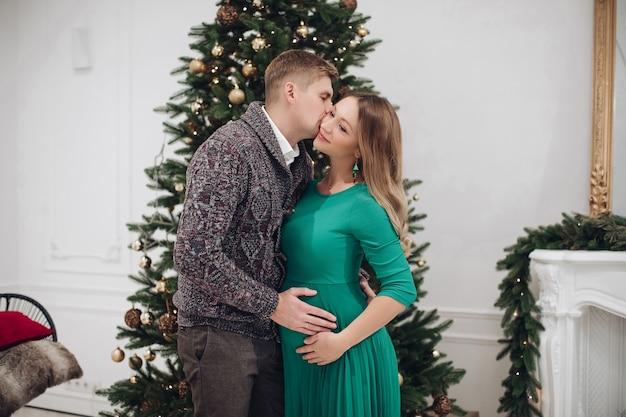 Casal feliz se beijando e sentindo amor na decoração luxuosa da árvore de natal