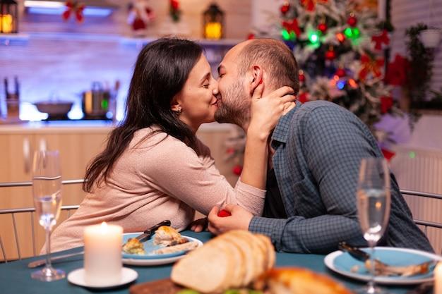 Casal feliz se beijando na cozinha de natal após pedido de casamento