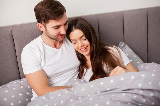 Casal feliz se divertindo na cama. íntimo, sensual, par jovem, em, quarto, desfrutando, um ao outro