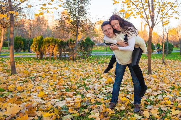 Casal feliz se divertindo no parque outono em um dia ensolarado de outono