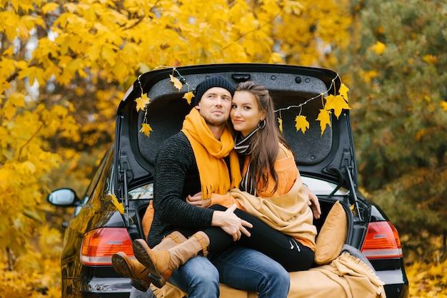 Casal feliz se senta no porta-malas de um carro, apreciando a vista do outono.
