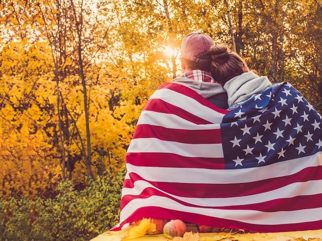 Casal feliz, segurando a bandeira dos eua