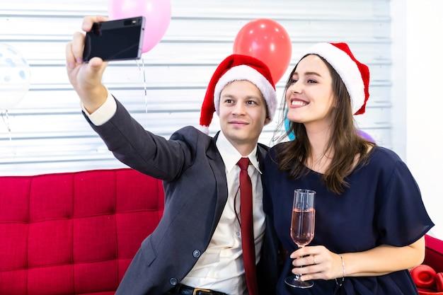 Casal feliz, segurando a taça de champanhe e fazendo um selfie