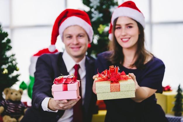 Casal feliz segurando a troca de presentes e dar um presente na árvore de natal da festa de natal e reveillon