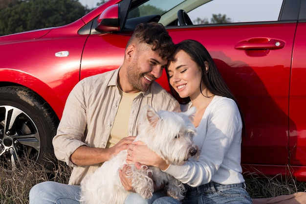 Casal feliz segurando cachorro tiro médio
