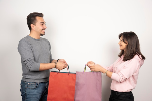 Casal feliz segurando sacolas de compras em branco.