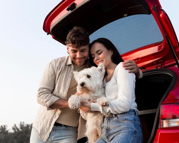 Casal feliz segurando um cachorro
