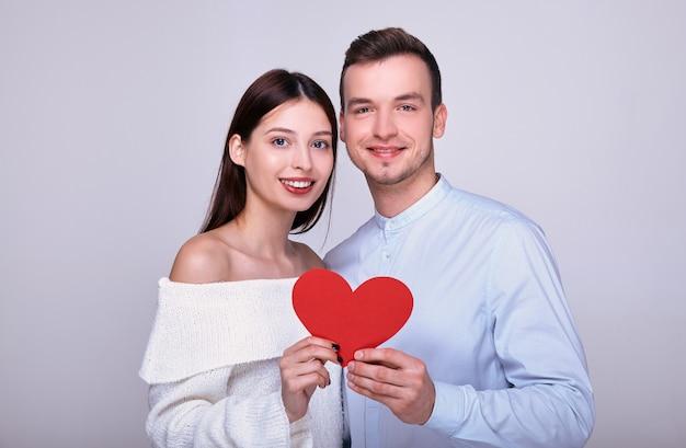 Casal feliz segurando um coração vermelho e sorrindo.