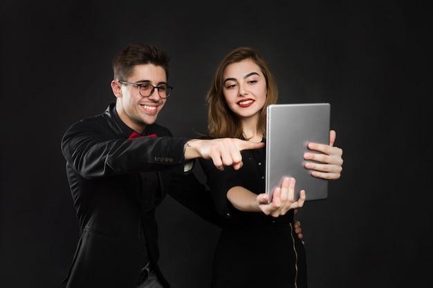 Casal feliz, segurando um tablet em fundo preto