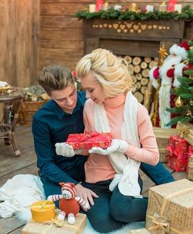 Casal feliz segurando uma caixa de presente e parabenizar um ao outro com o natal.
