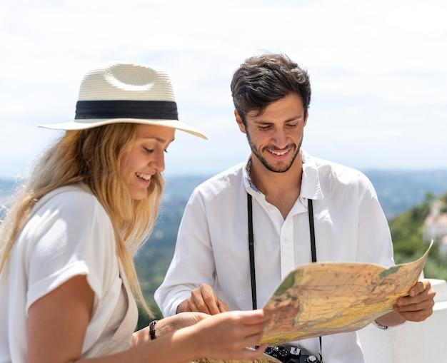 Casal feliz segurando uma foto média do mapa