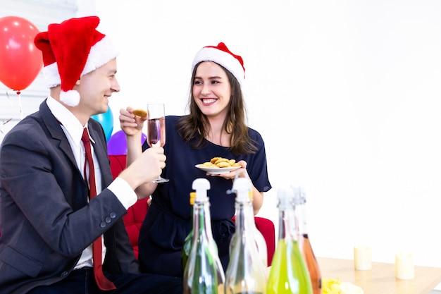 Casal feliz, segurando uma taça de champanhe e comer biscoitos no natal