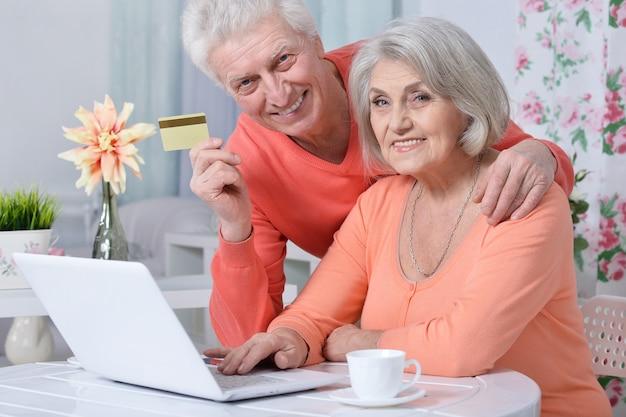 Casal feliz sênior com laptop e cartão de crédito em casa