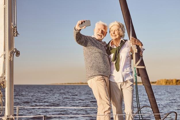 Casal feliz sênior em pé ao lado do barco à vela ou do convés do iate flutuando no mar, homem e mulher