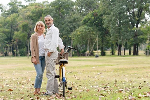 Casal feliz sênior em pé relaxa depois de andar de bicicleta no parque.