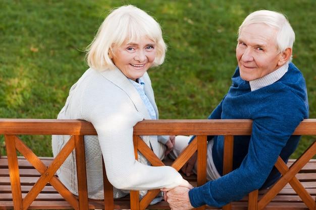Casal feliz sênior. retrovisor de um feliz casal de idosos de mãos dadas e olhando para a câmera com um sorriso enquanto estão sentados no banco do parque juntos