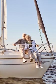 Casal feliz sênior sentado ao lado do barco a vela ou do convés do iate flutuando no mar, homem e mulher
