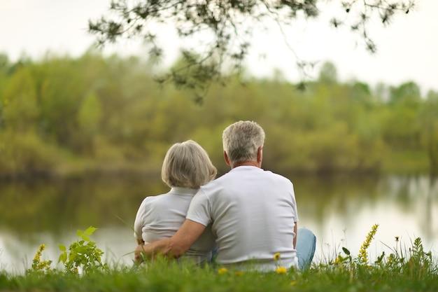 Casal feliz sênior sentado no verão perto do lago