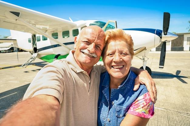 Casal feliz sênior tomando selfie com avião ultraleve privado para excursão ao redor do mundo